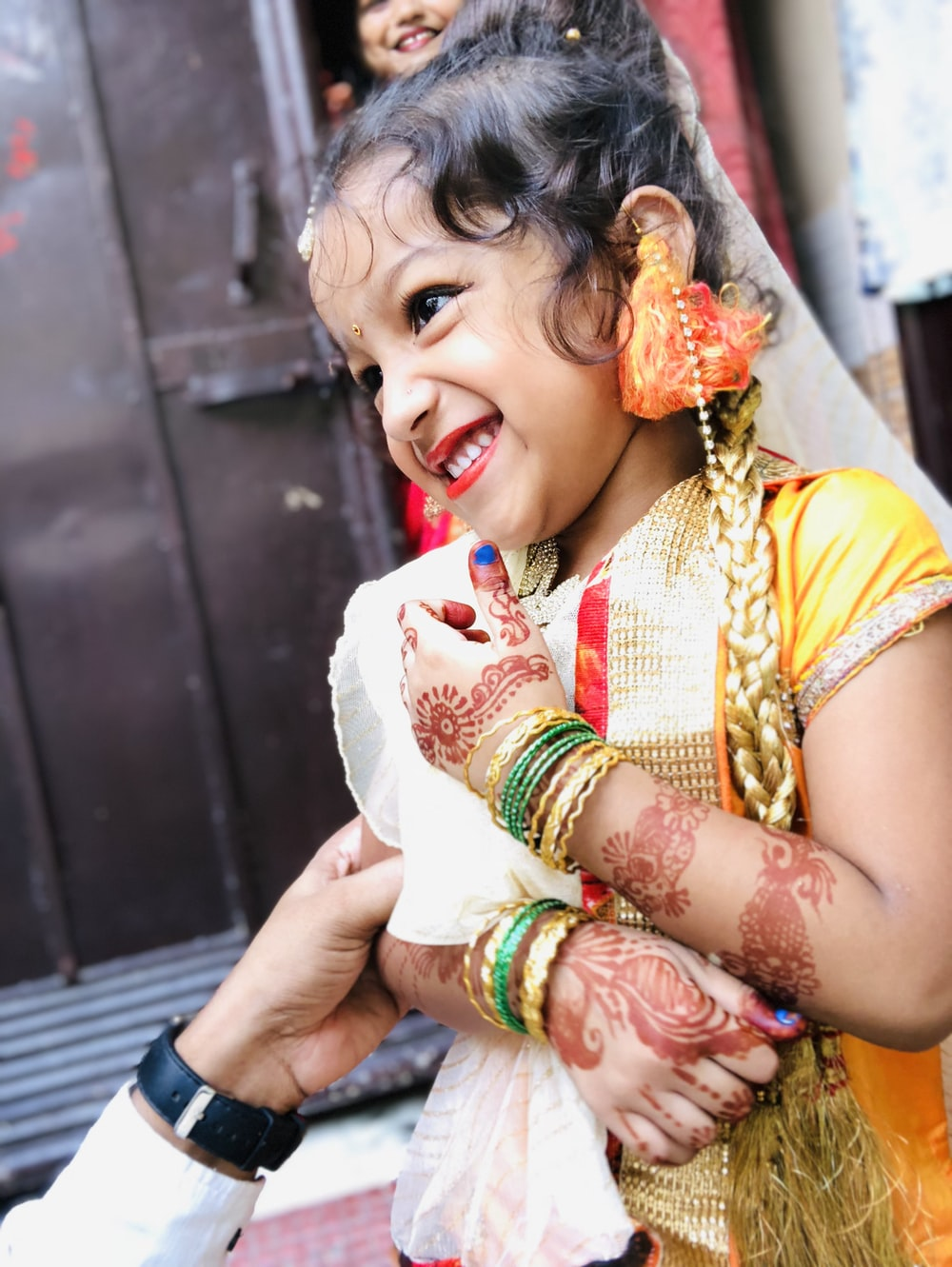 smiling girl wearing gold cap-sleeved dress with red mehndi arm tattoos