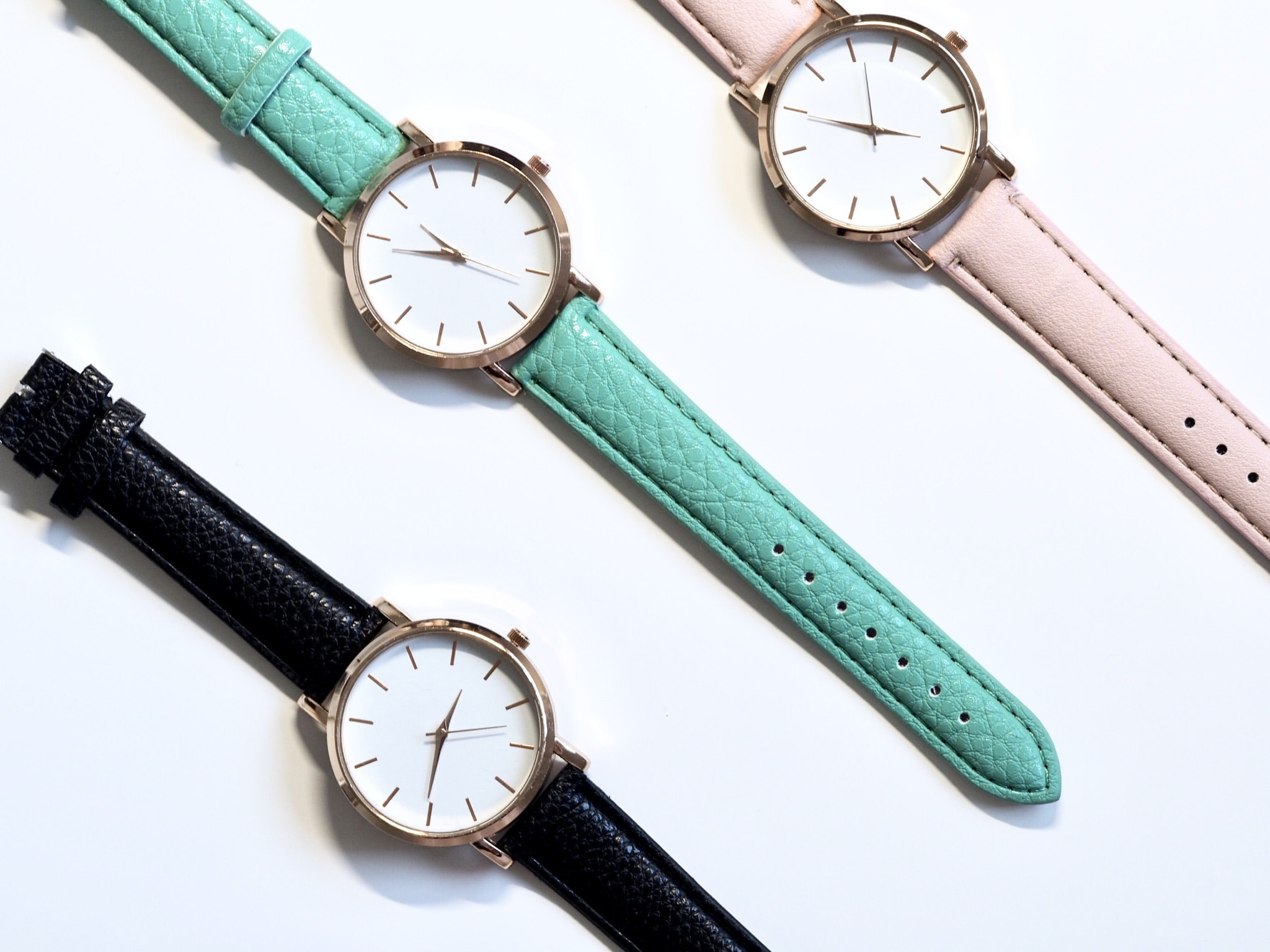 three round assorted-color analog watches with leather straps