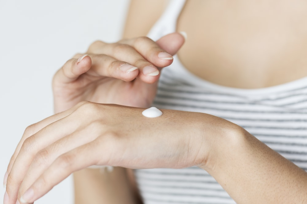 white cream on woman's hand