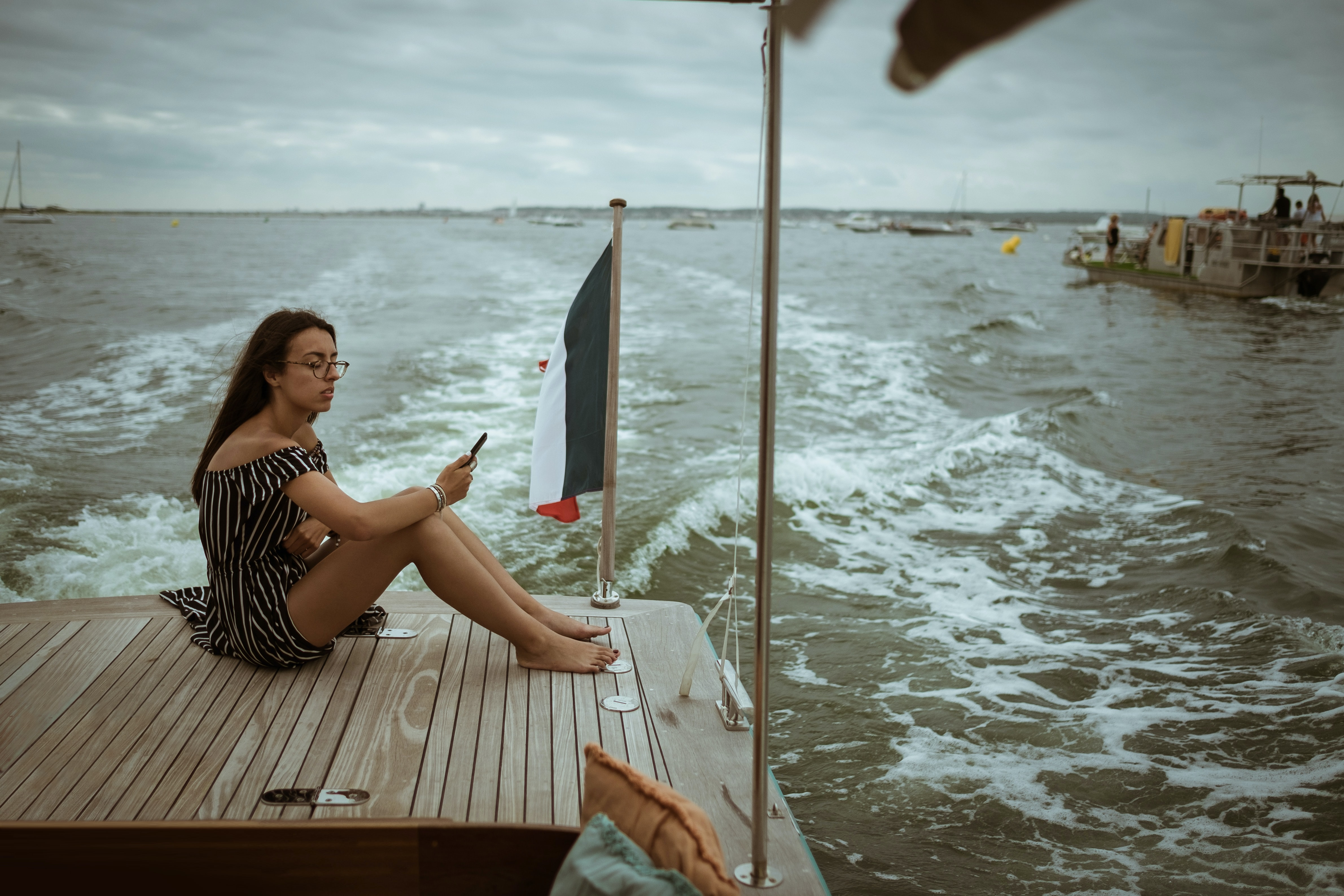 woman sitting on wooden deck above body of water