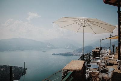 white patio umbrella beside chair during daytime