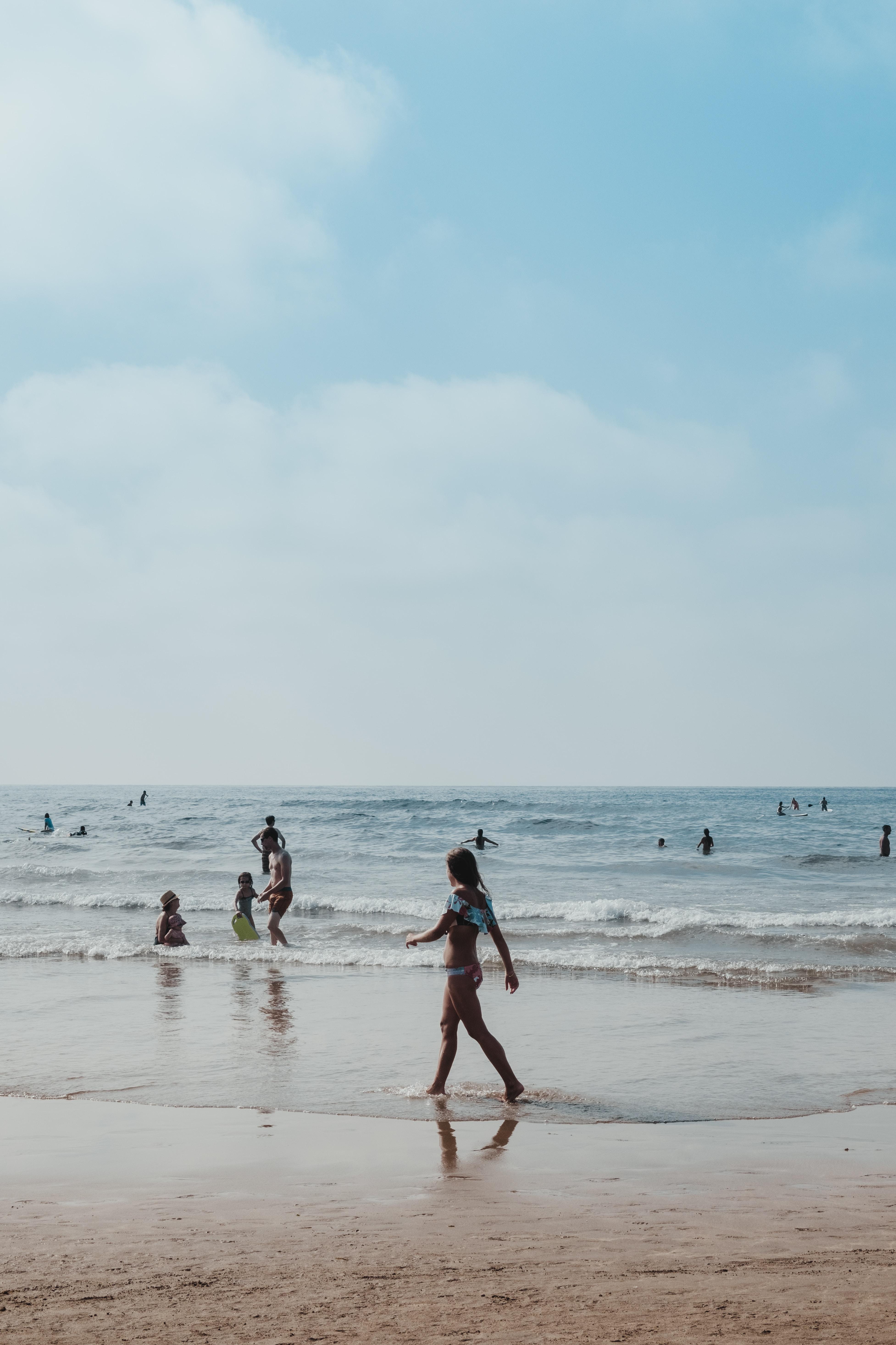 woman walking on seashore during daytime