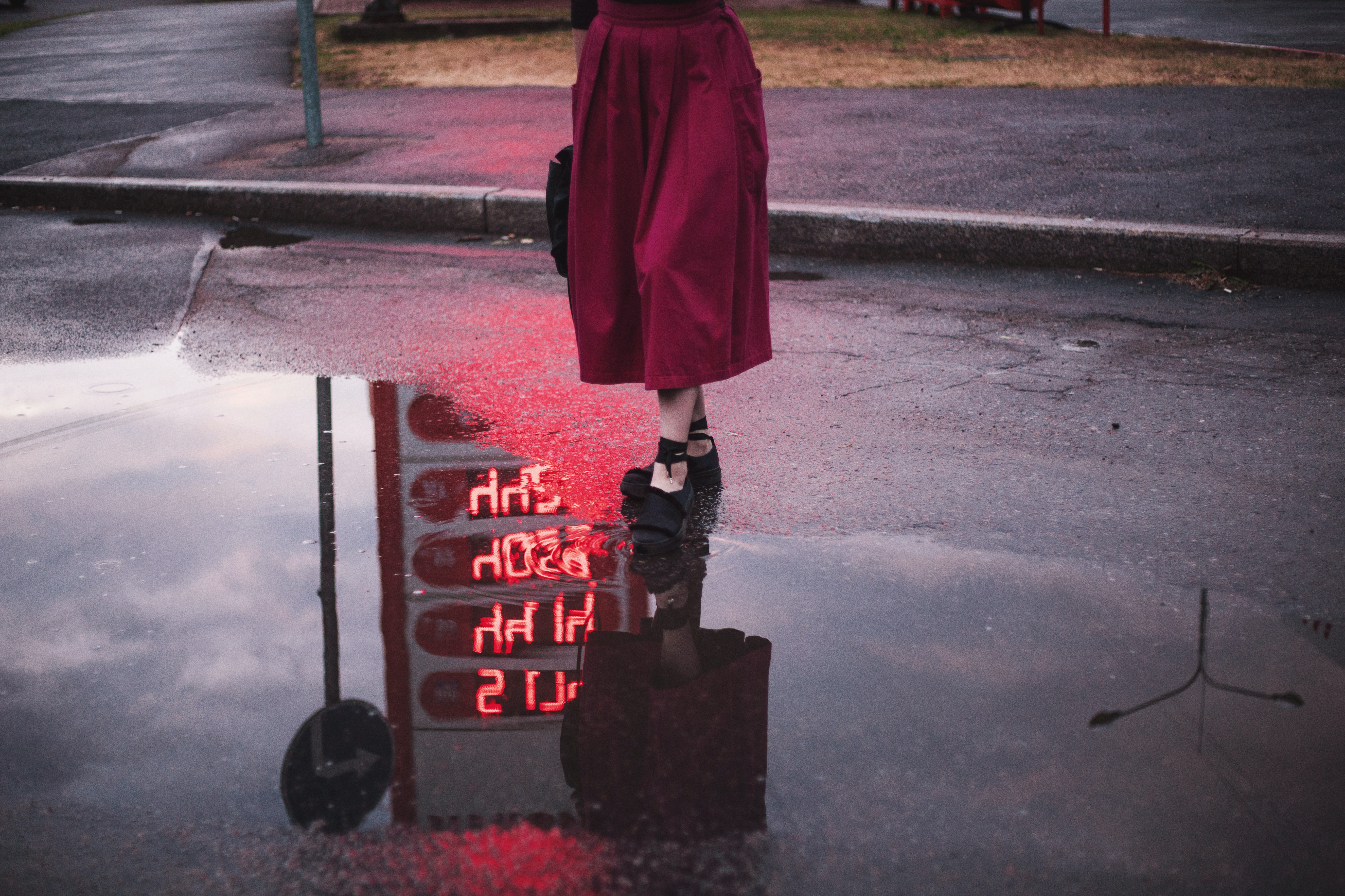 woman standing on road beside water reflecting gasoline station's price signage