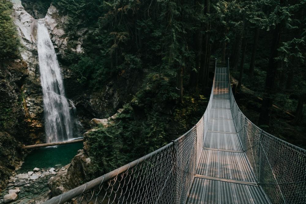 gray wire bridge near waterfalls