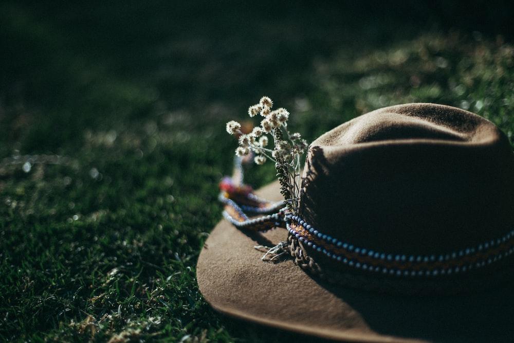 brown fedora hat on grass field