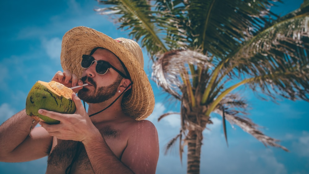 man standing holding green coconut during daytime