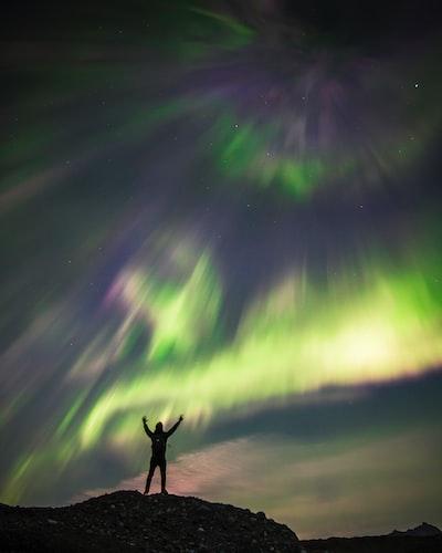 silhouette photography of man standing under sky phenomenon