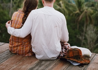 man and woman sitting on brown wooden platform
