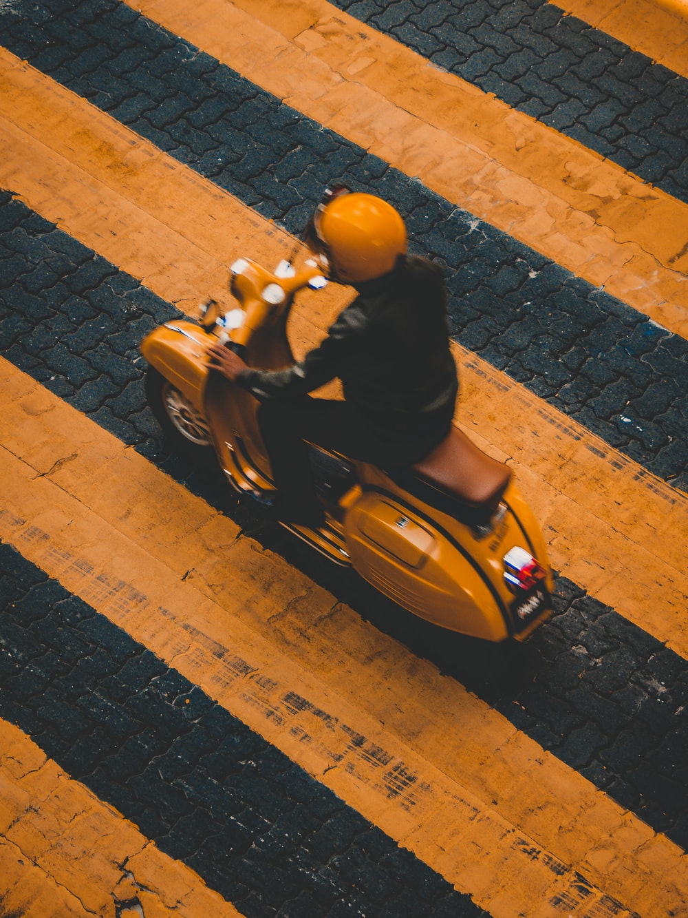 man riding on yellow motor scooter on striped yellow lines