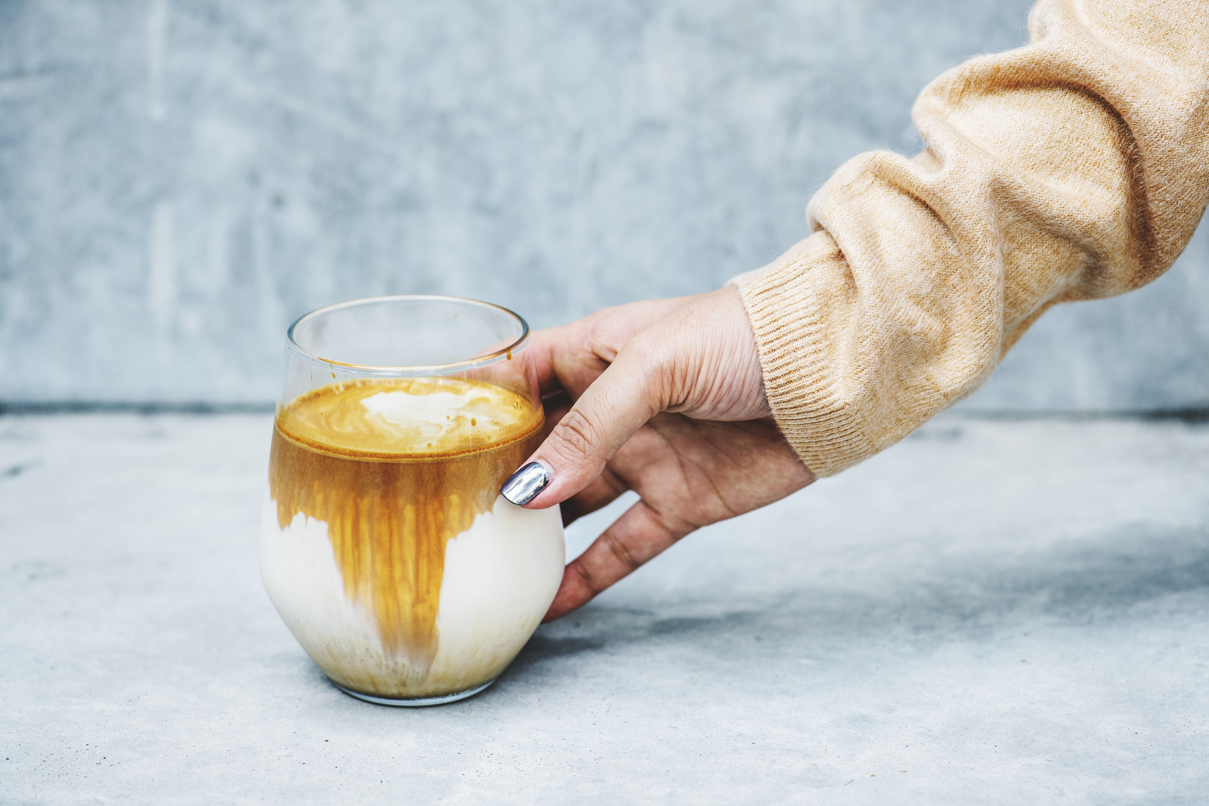 person holding clear glass cup with brown and white liquid