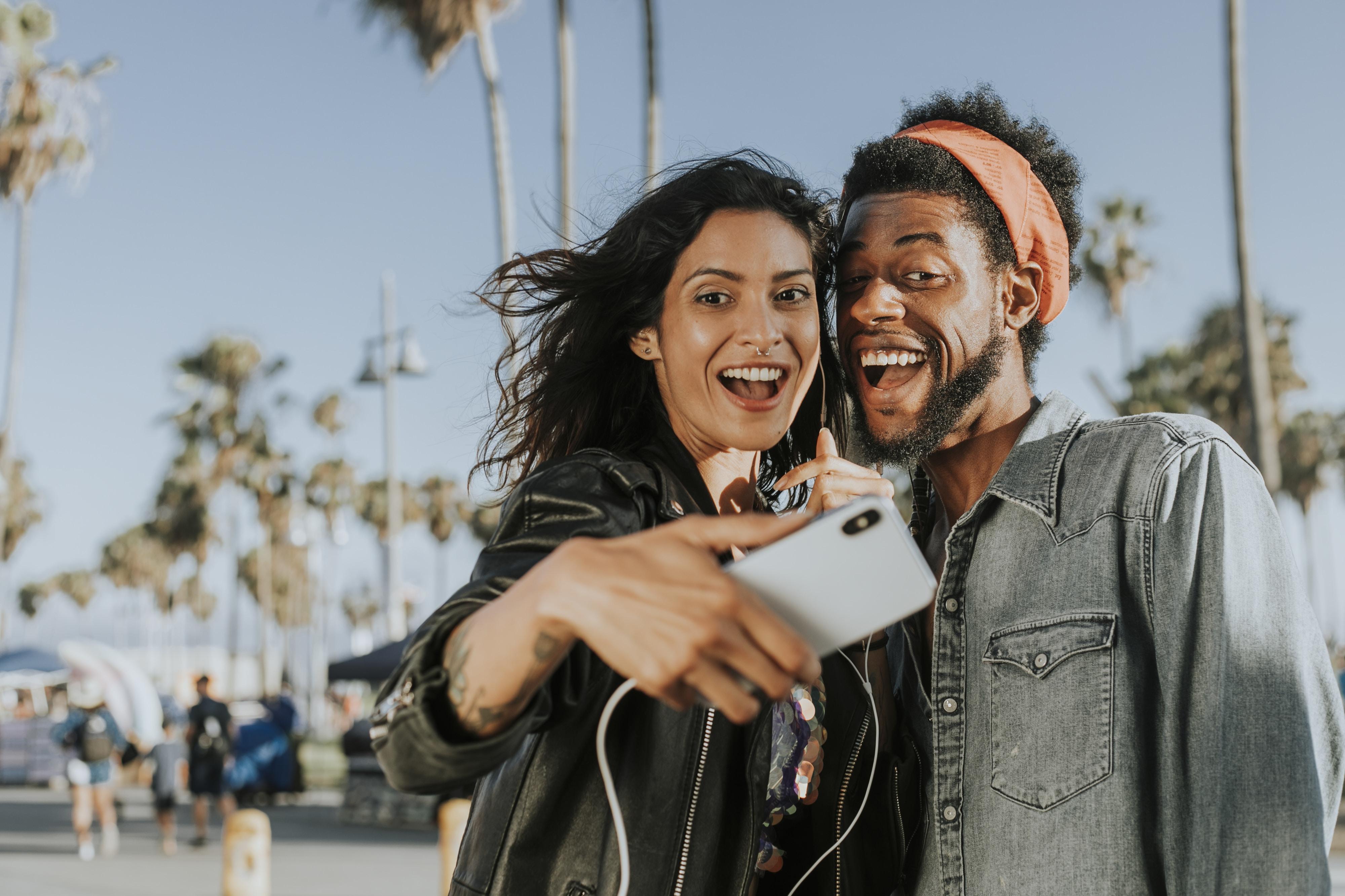 woman taking wacky pose beside man in gray denim top
