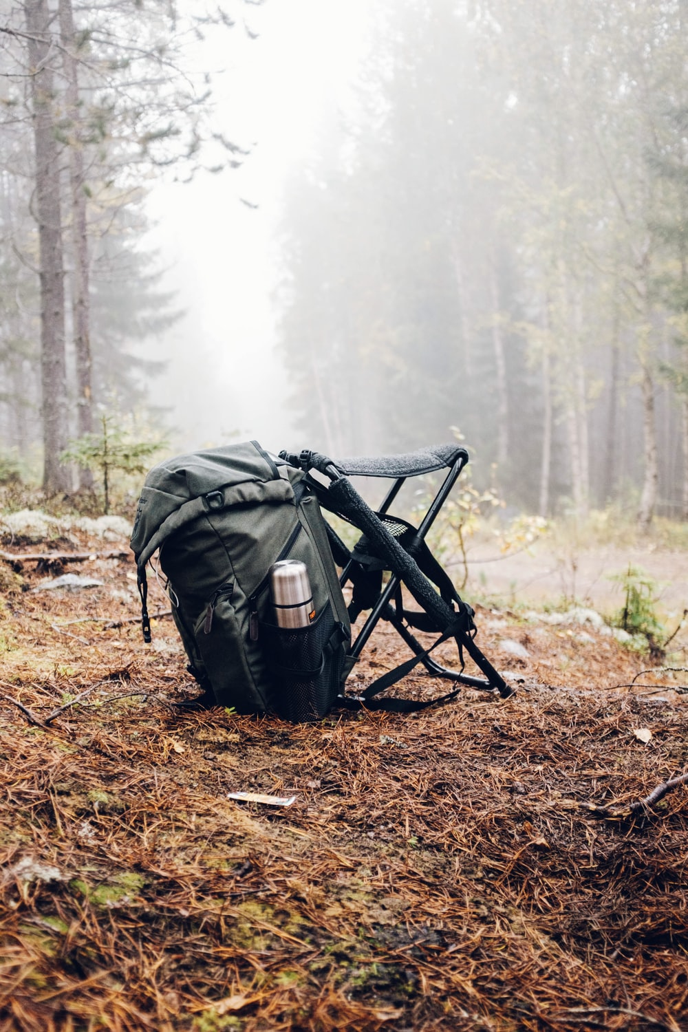 black and gray backpack with camping chair on forest