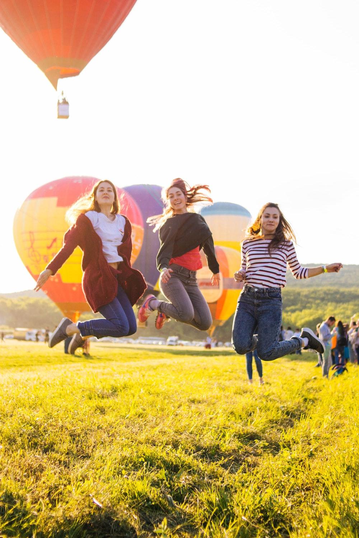 three women jumping above green grass