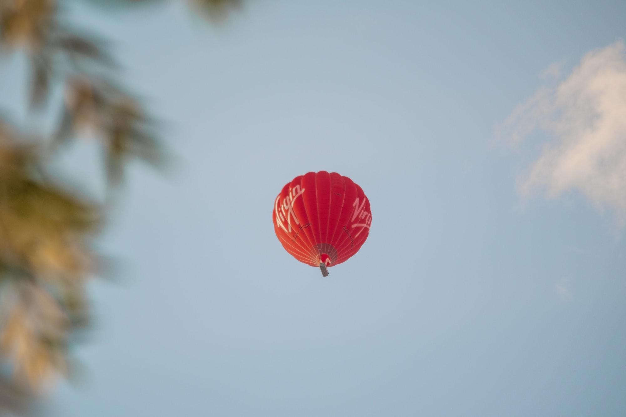A Virgin Group hot air balloon high in the summer sky above New Bradwell / Wolverton, Milton Keynes.