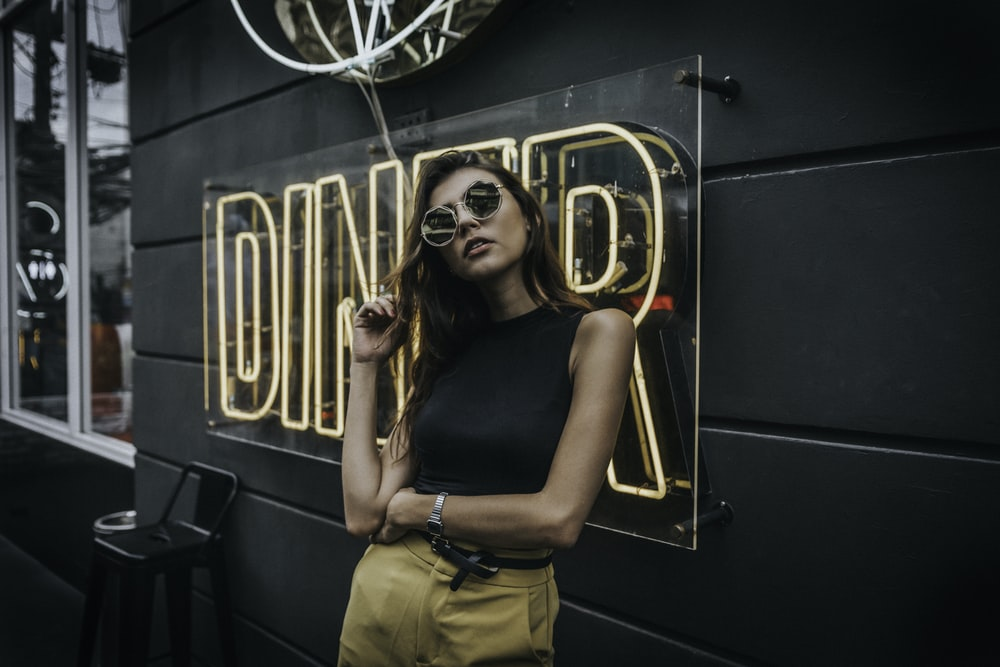 woman standing in front of Diner neon signage