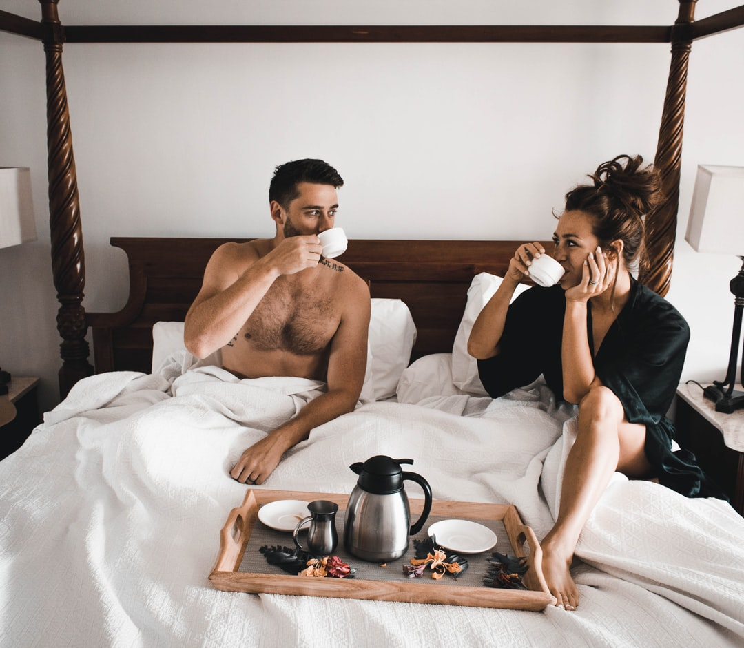 A couple drinking out of cups, in a bed of white sheets and a tray with coffee and flowers