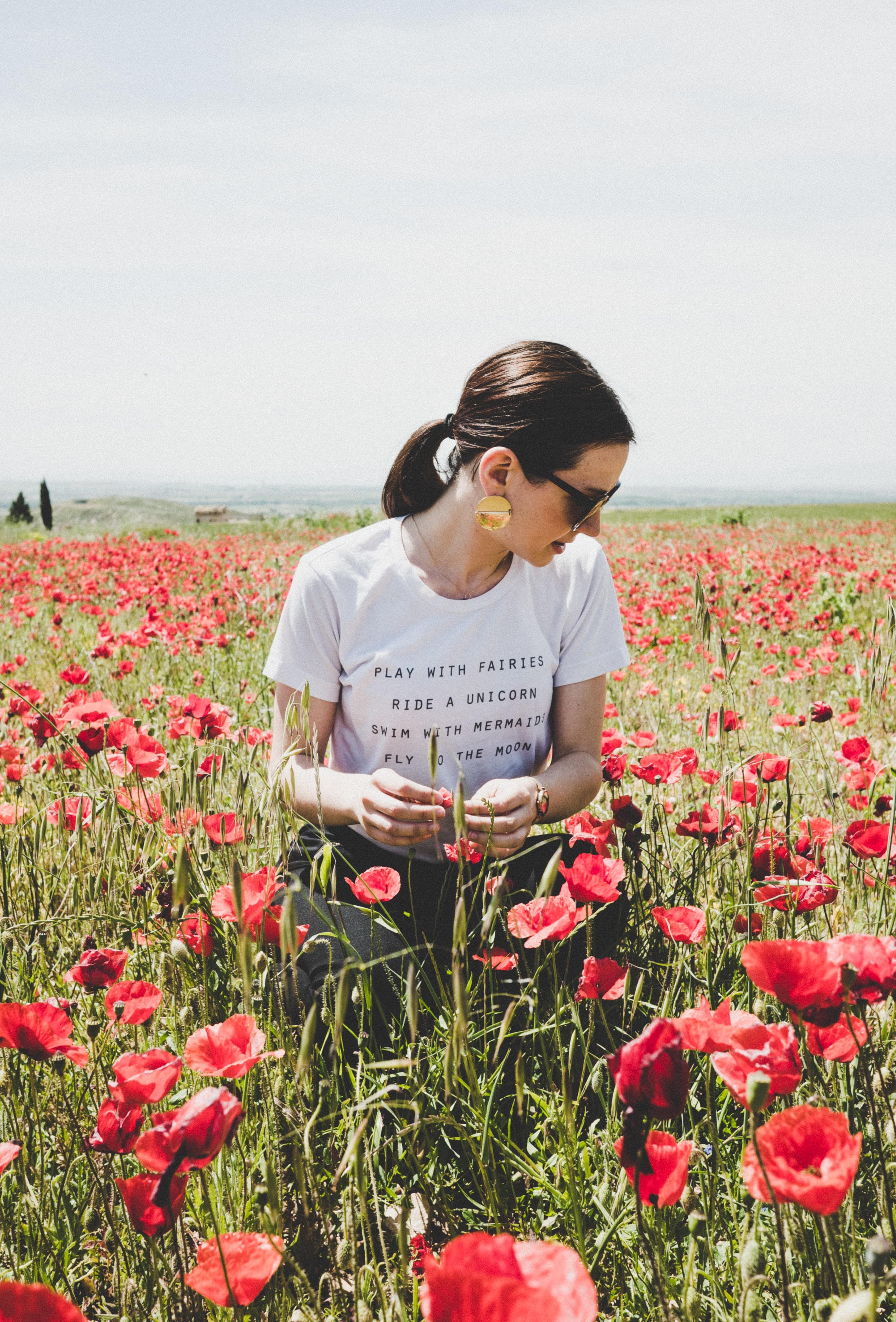 woman sitting on common poppy field