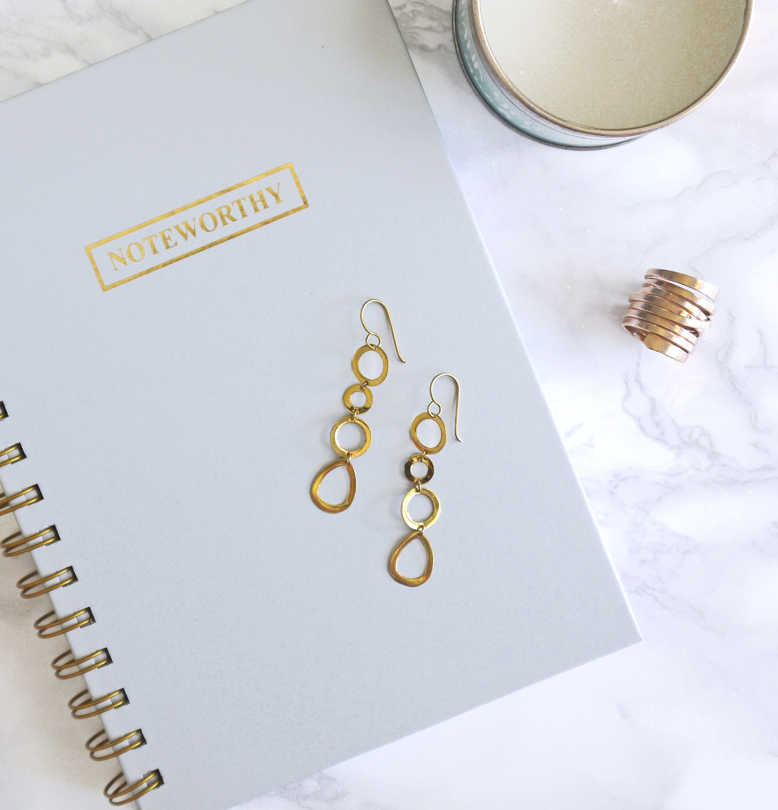 pair of gold-colored dangling hook earrings on top of spiral notebook
