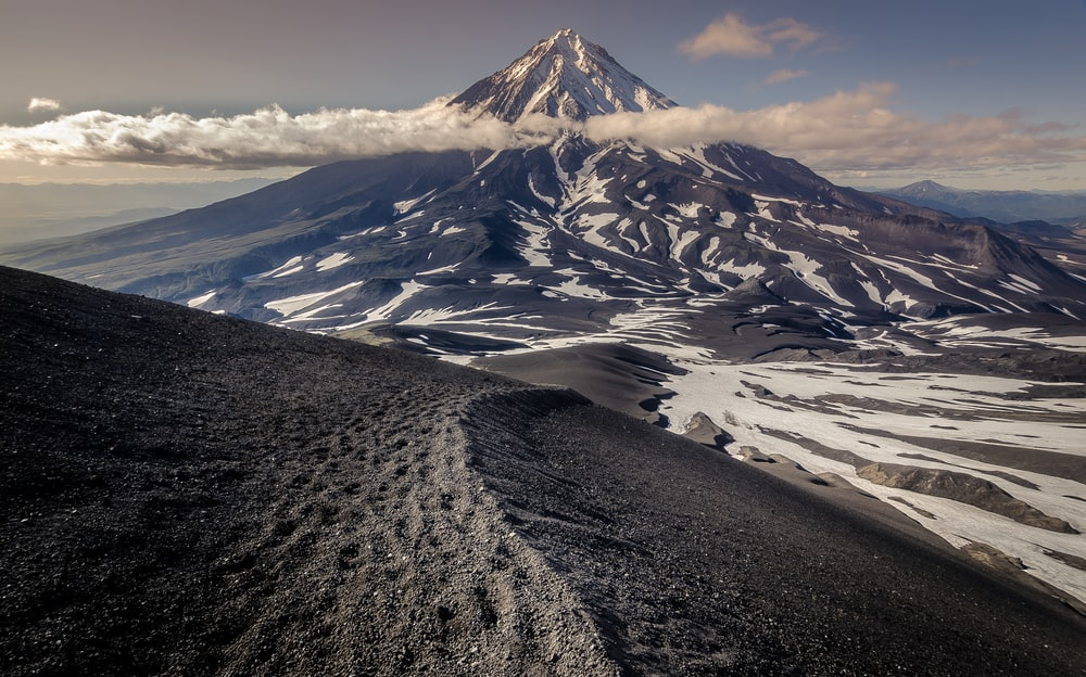 cone-shaped mountain and ice field at daytime