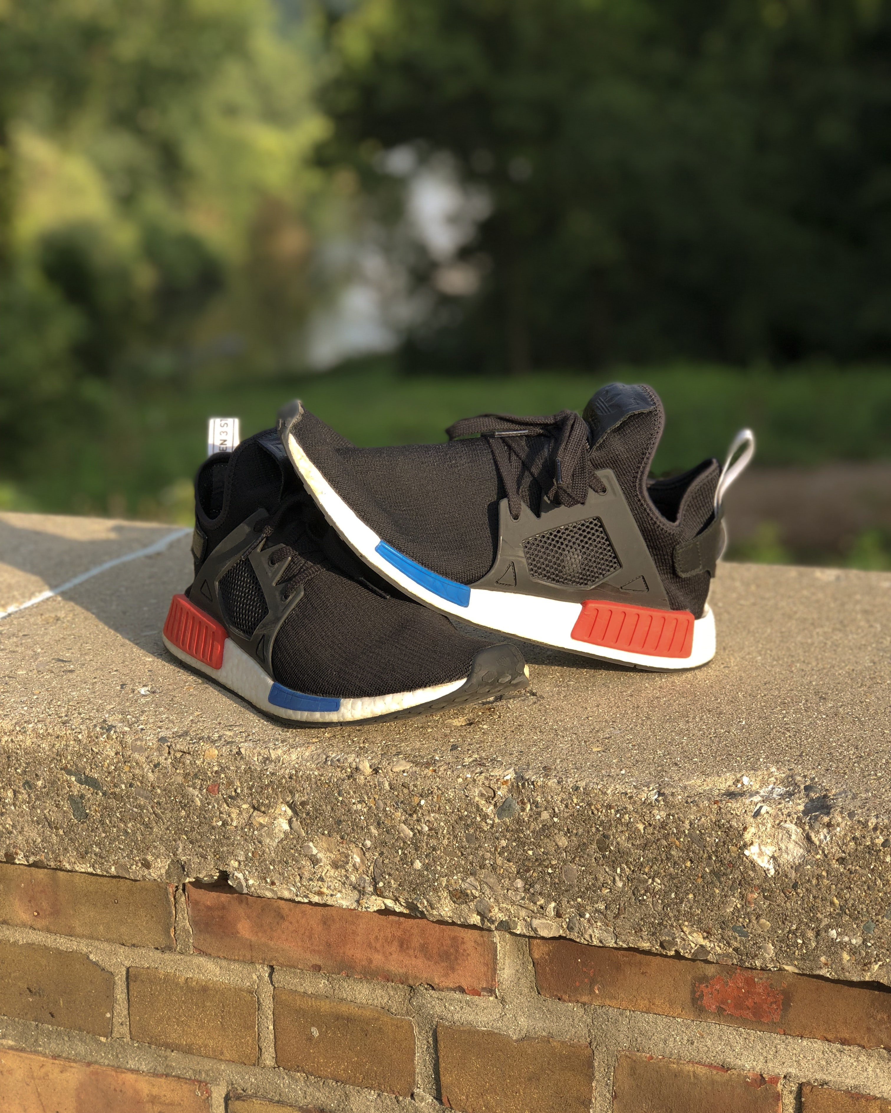 pair of black-and-white adidas NMD on gray concrete fence