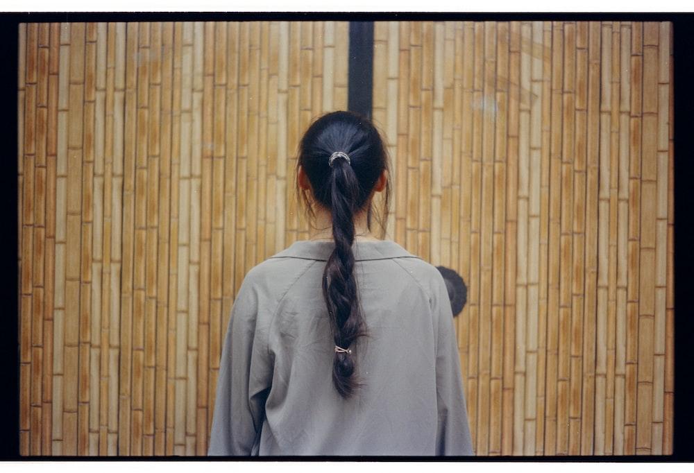 woman wearing gray top facing wooden wall