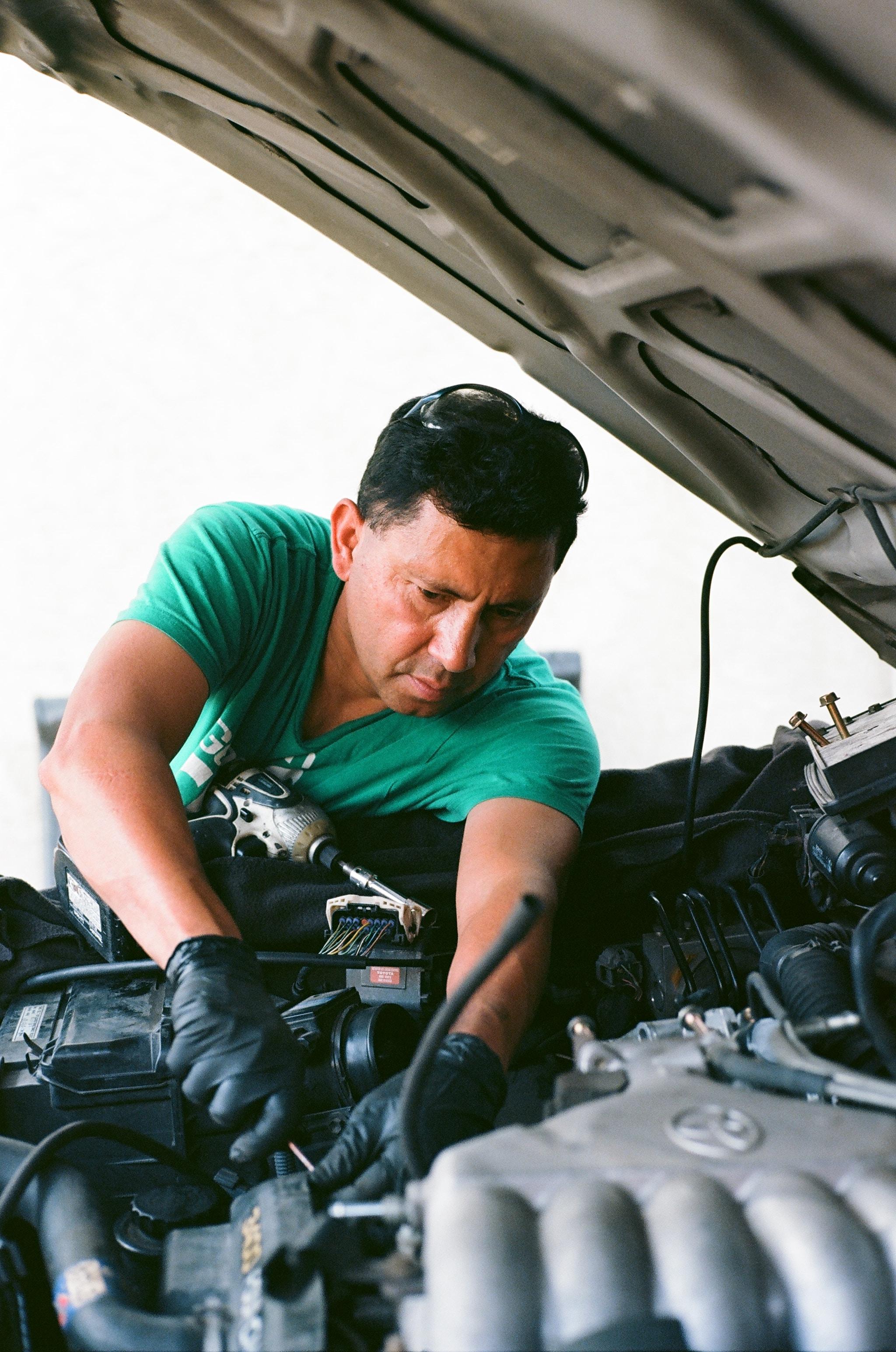 man repairing vehicle engine