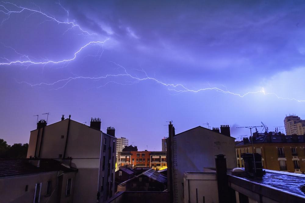 white buildings under lightnings