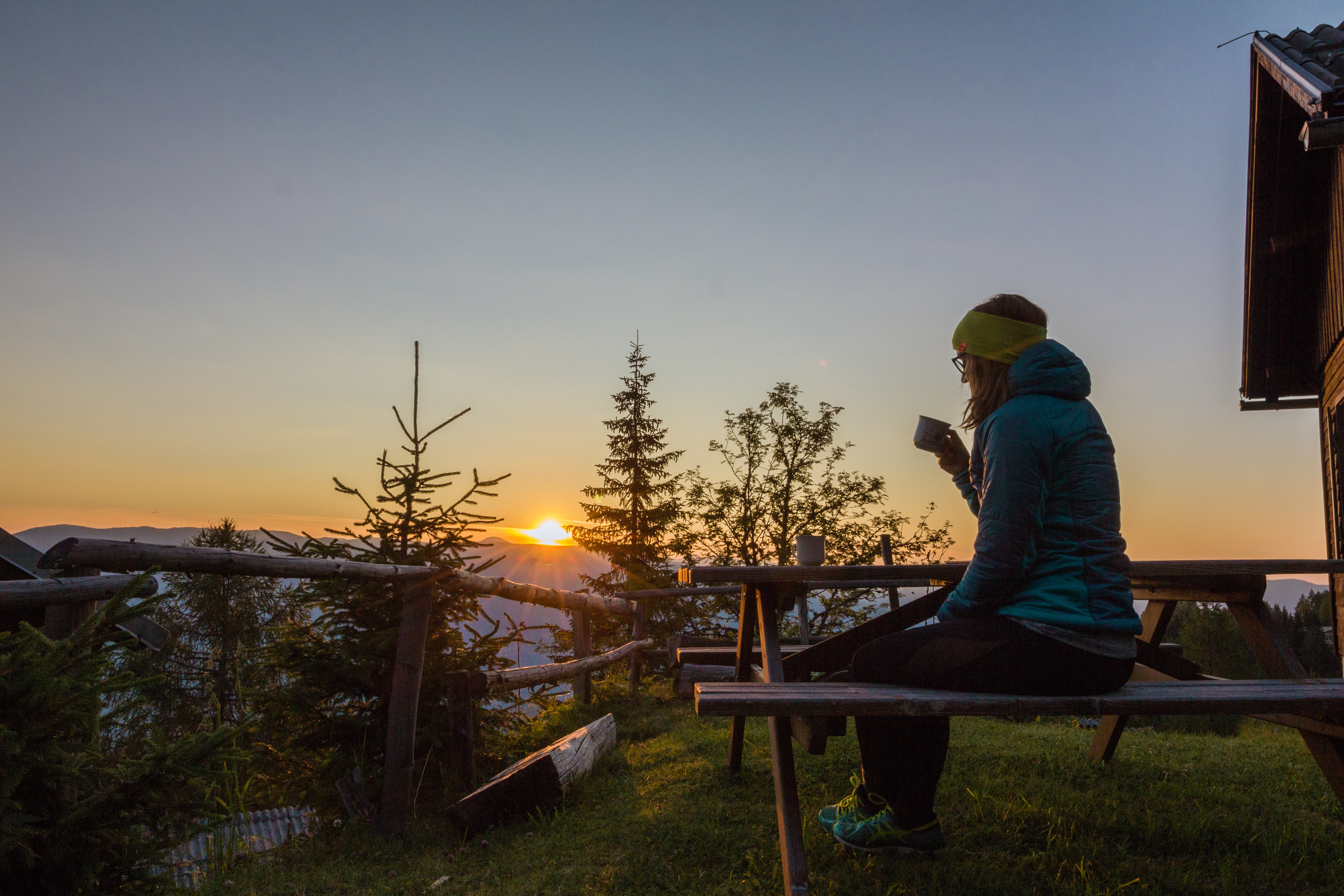 woman in blue bubble jacket sitting and having a coffee on mountain during sunrise