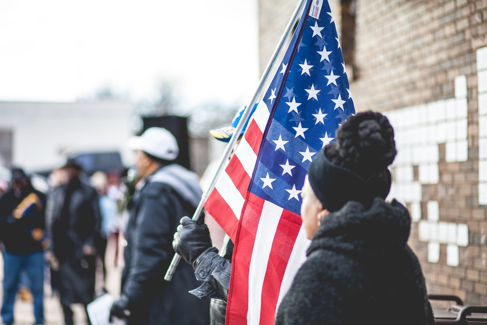 woman standing beside person holding flag of America