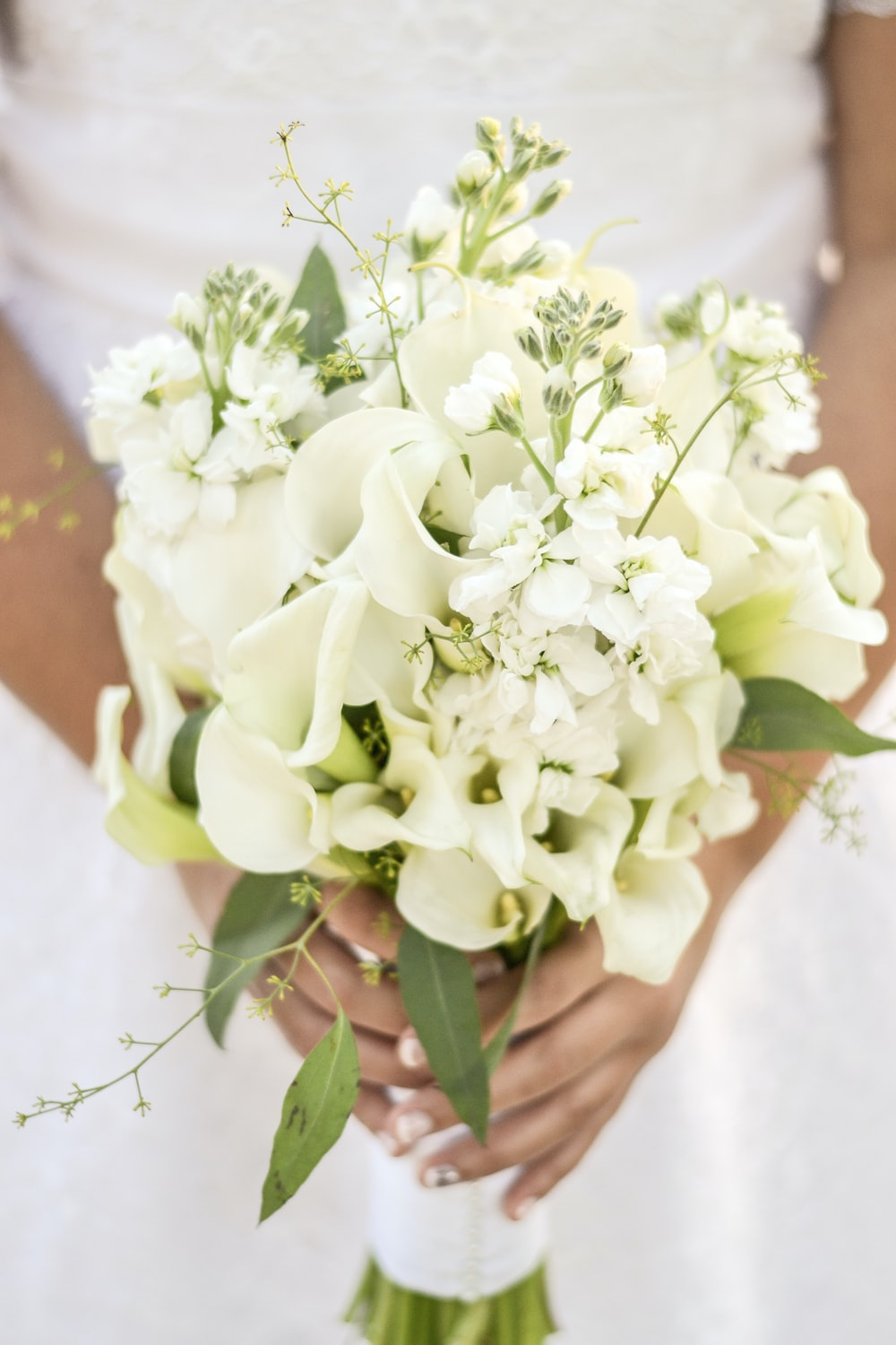 selective focus photography of woman holding bouquet of flowers