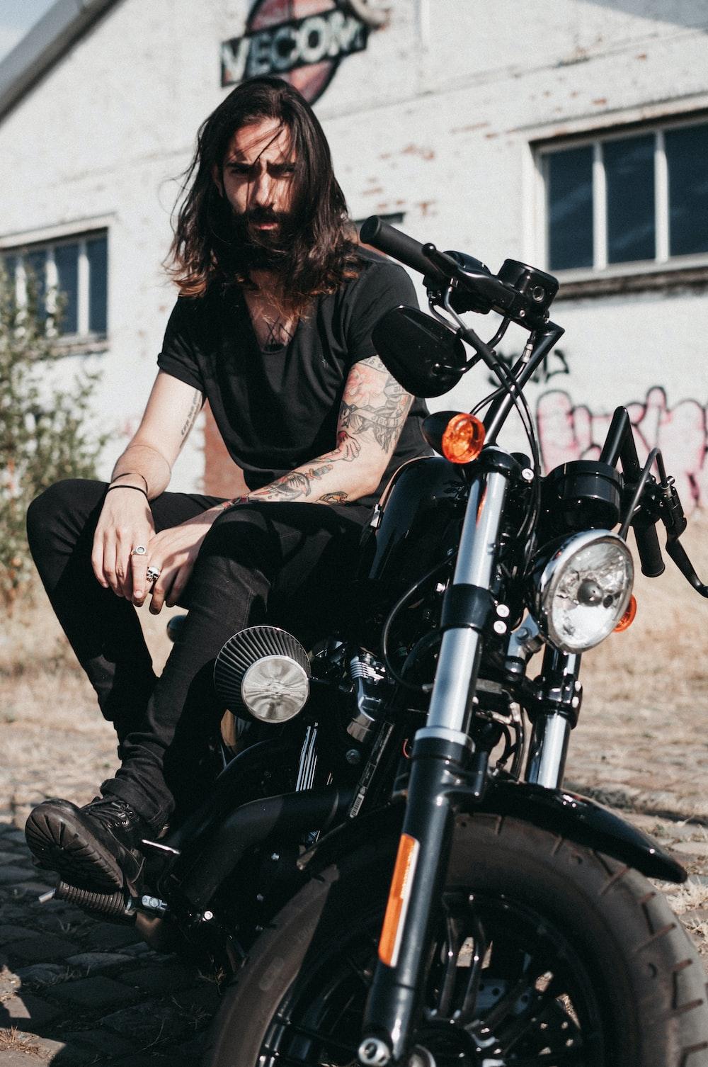 man sitting on black cruiser motorcycle