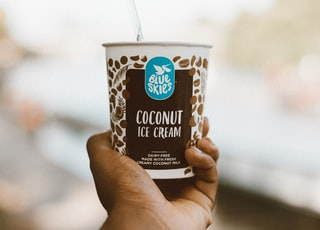 person holding Blue Skies coconut ice cream cup