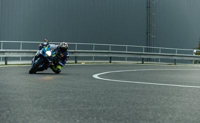 man riding motorcycle suzuki teams background