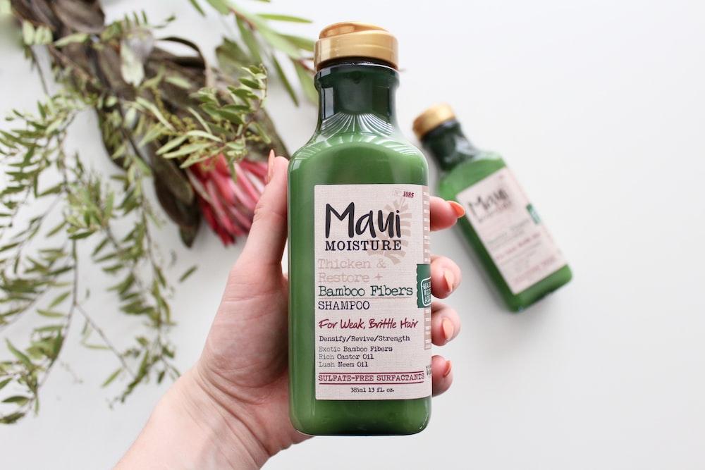 person h olding Maui moisture bottle