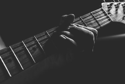 grayscale photo of person holding guitar neck and strings