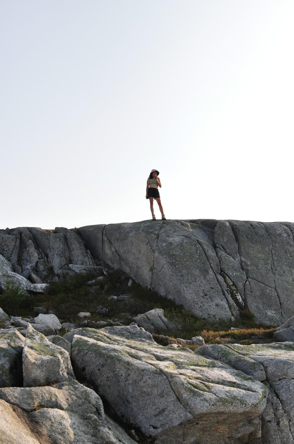 woman standing on grey rock on mountain
