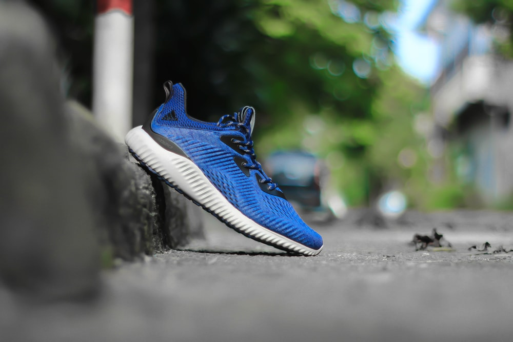 selective focus photography of unpaired blue and white adidas running shoe leaning on concrete pavement at daytime