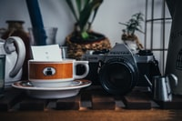 gray and black Pentax MILC camera beside round white and brown ceramic teacup on top of round white and brown saucer on top of table