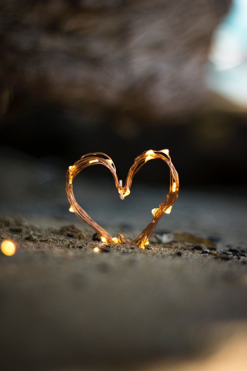 close-up photography of heart shaped fairy lite on brown sand