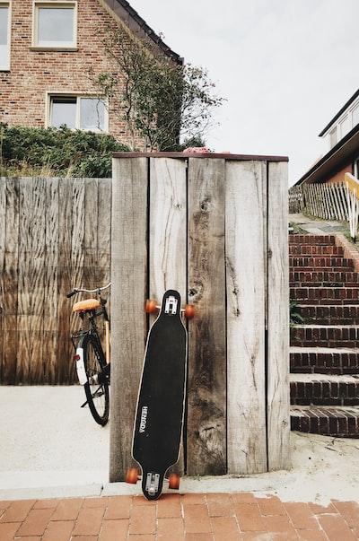 black longboard leaning on brown wooden board