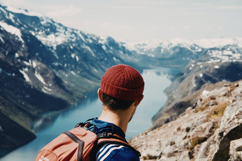 man white red head cap and orange backpack walking along mountain cliff with lake below