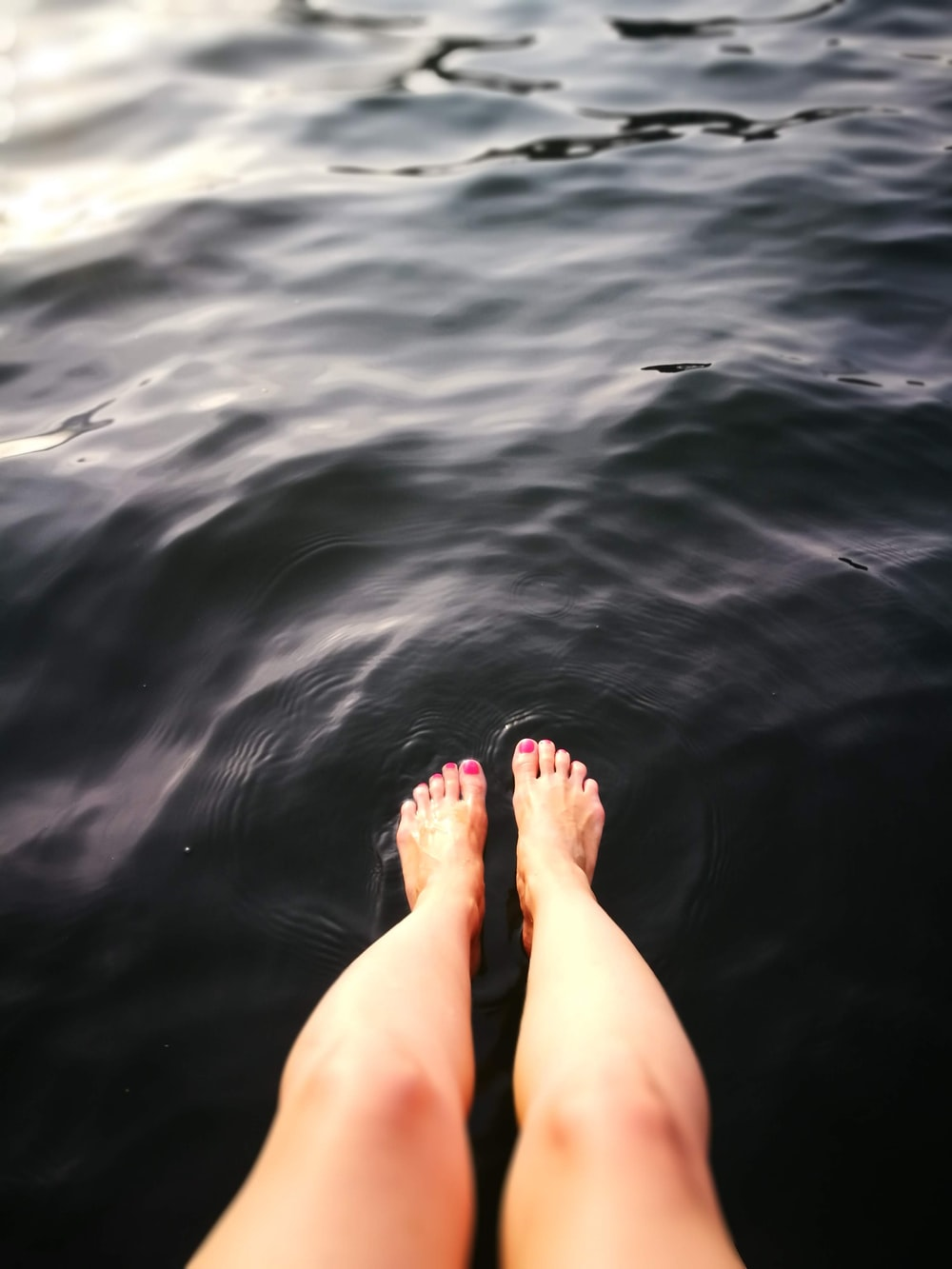 person feet on calm body of water
