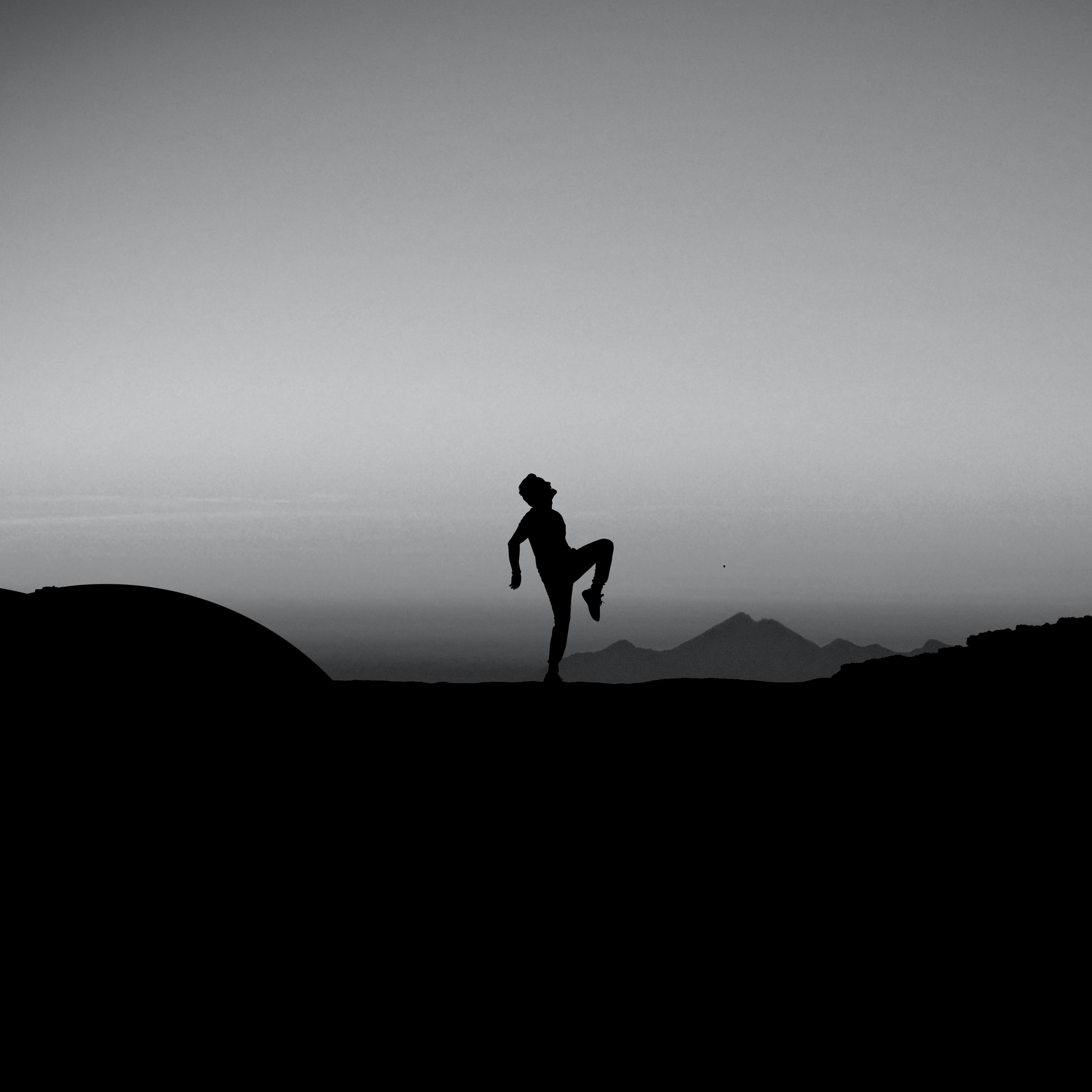 silhouette photography of man standing with one leg on ground
