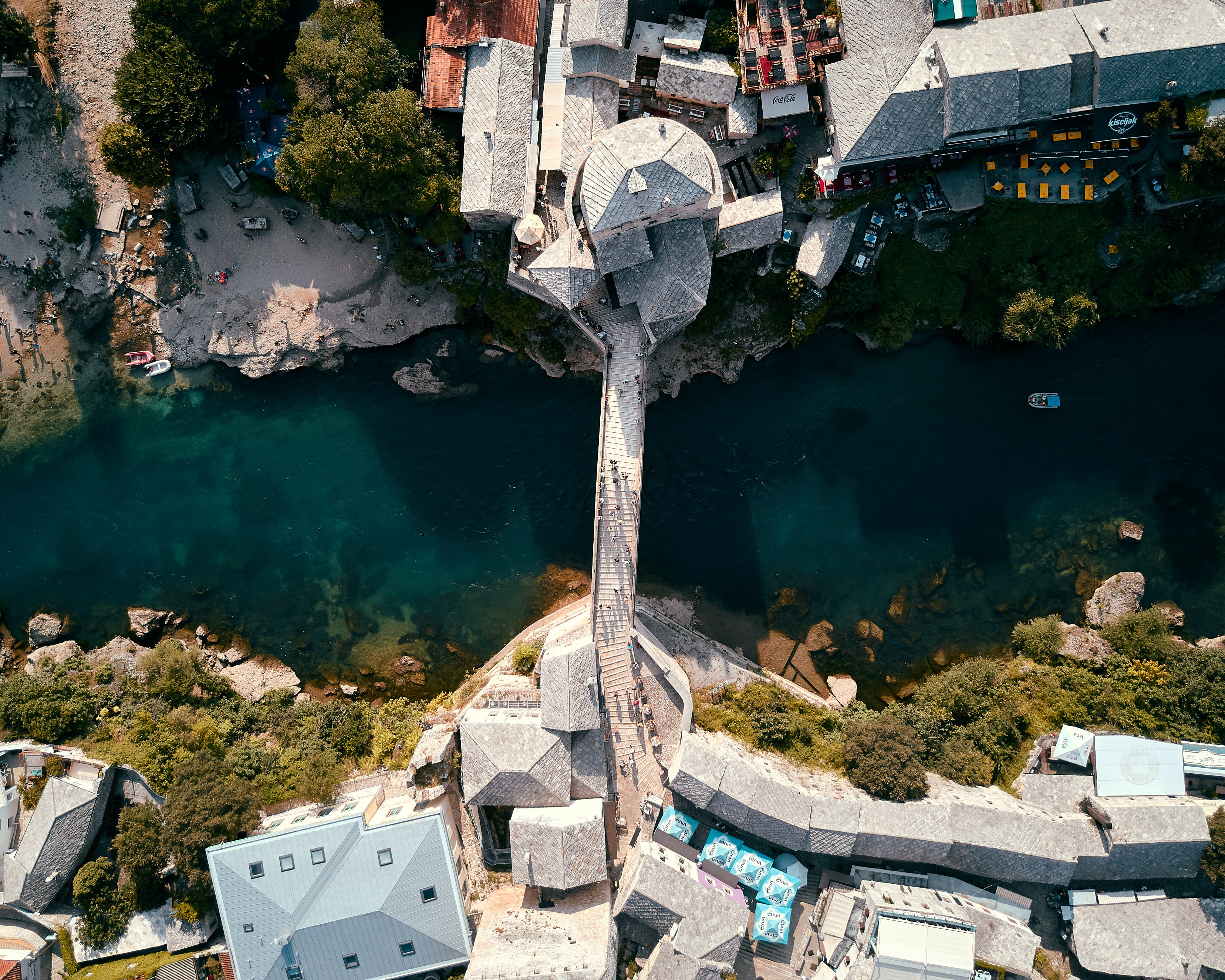 top view photo of concrete bridge connecting two village at daytime