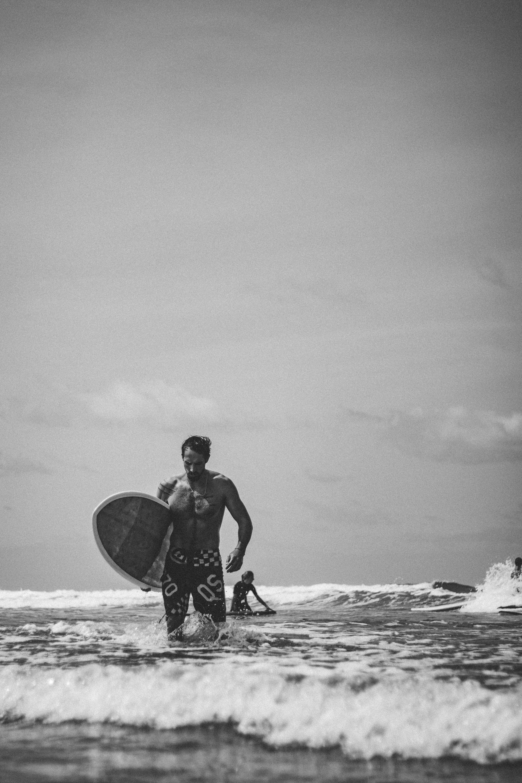 man standing on seashore holding surfboard