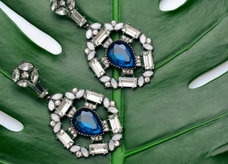 pair of silver-colored earrings with blue gemstone