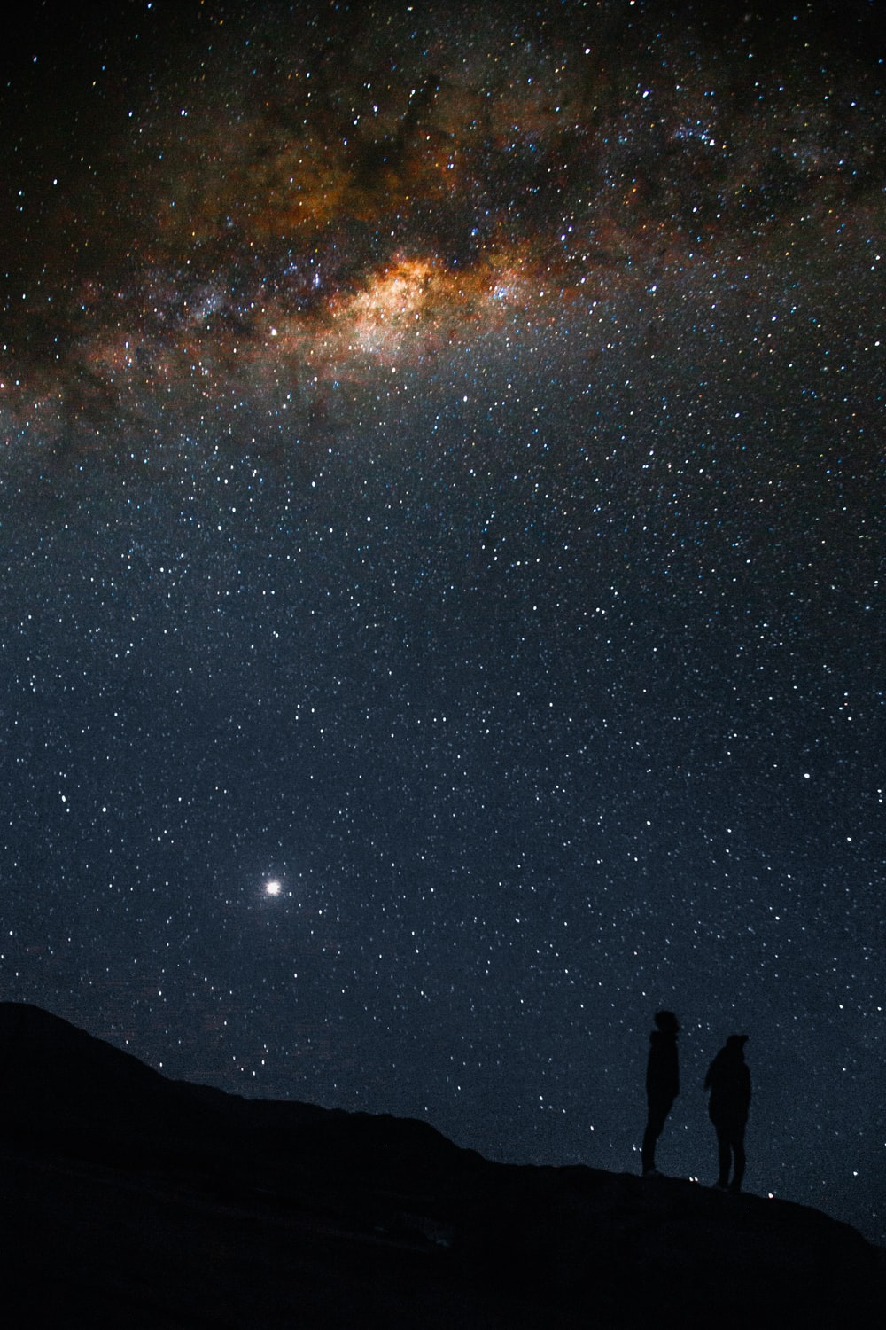 silhouette of two person standing under Milky Way sky during nighttime