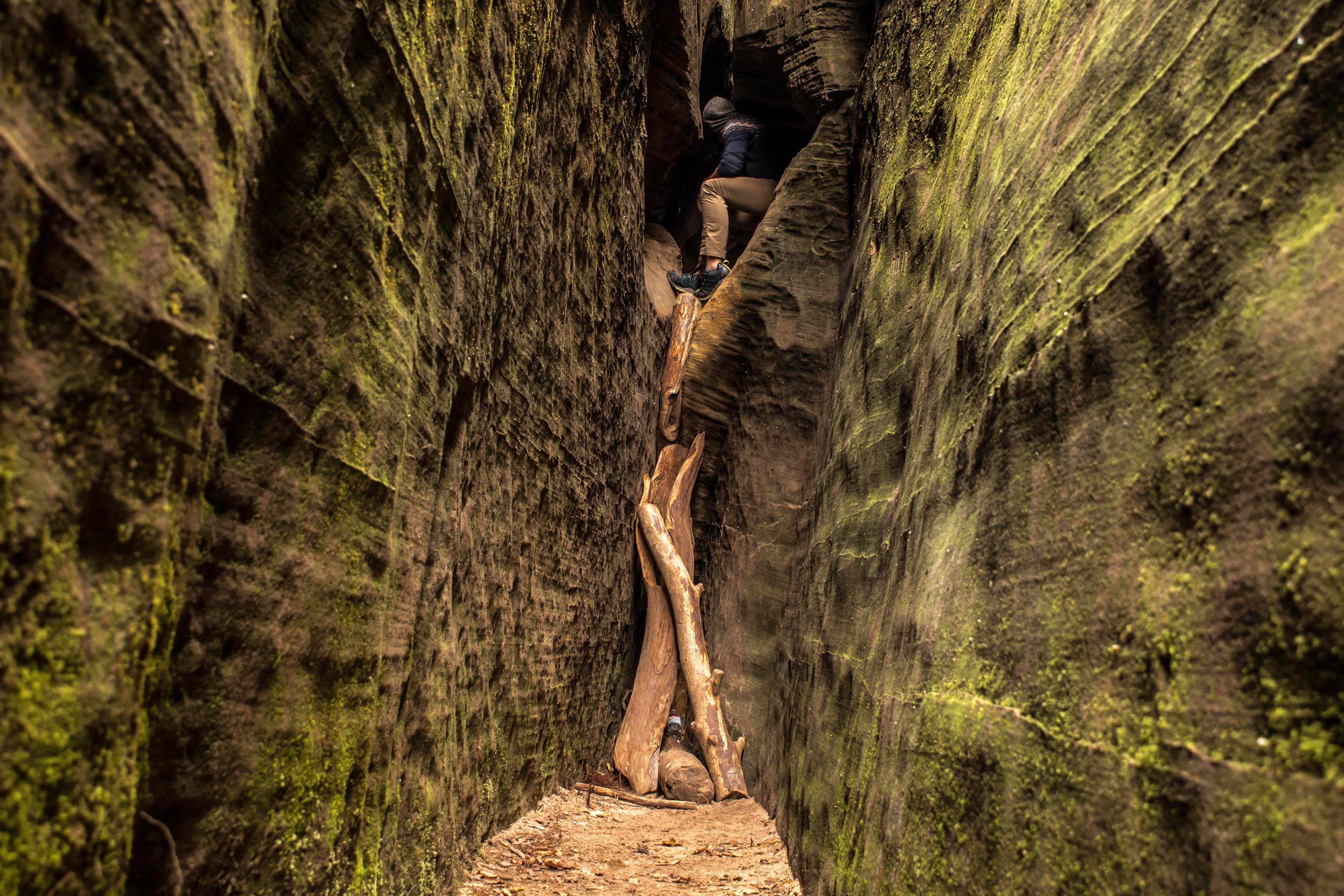 man inside cave between narrow pathway