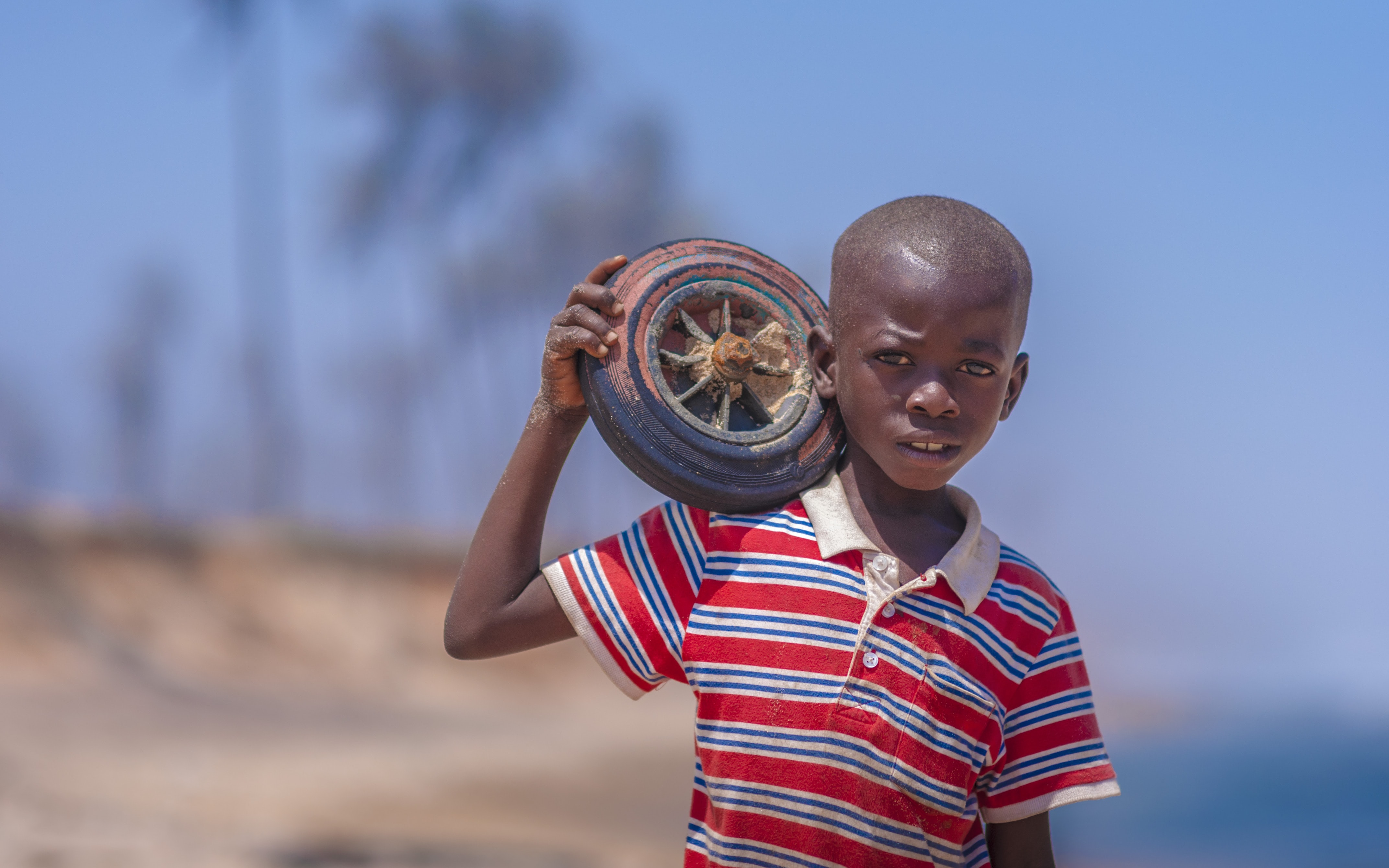 selective focus photography of boy carrying wheel