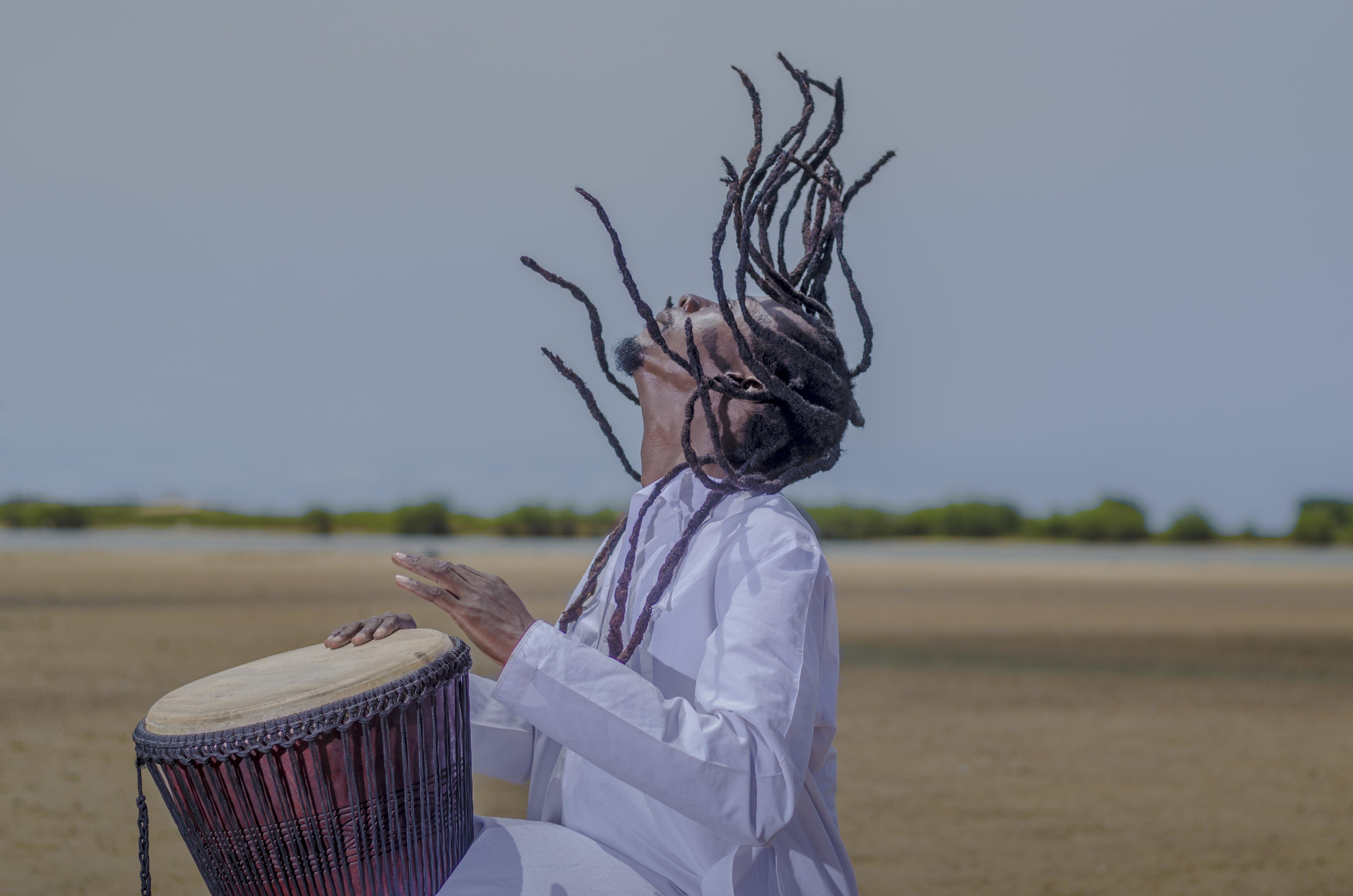 man playing musical drum